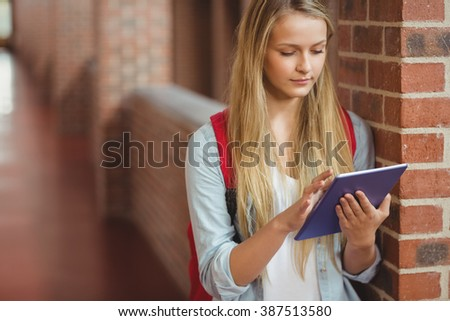 Student using tablet in the hallway at university - stock photo