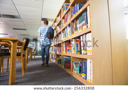 Student walking away in the library at the university - stock photo