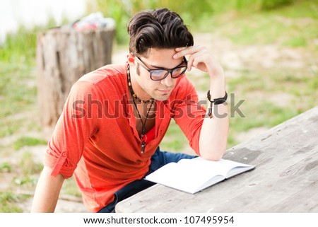 student wearing glasses reading in the park - stock photo