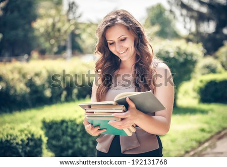 student with a book on street - stock photo