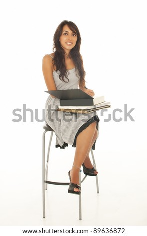 Student with a notebook sits on a chair isolated a white backgro