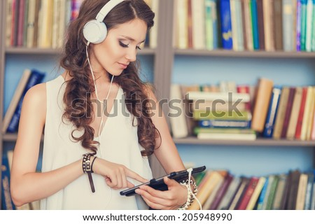 Student with headphones in library - stock photo