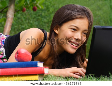 Student with laptop smiling while chatting / checking email in the park. Beautiful mixed race caucasian / asian model. - stock photo