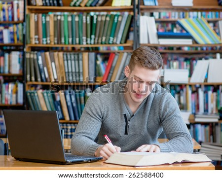 Student with laptop studying in the university library - stock photo