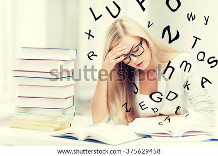 student with pile of books and notes studying indoors - stock photo