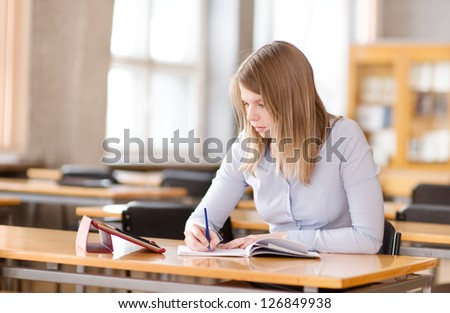 student with tablet computer in library - stock photo