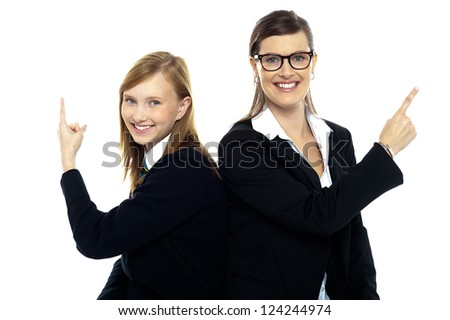 Student with teacher, back to back. Pointing away on white background. - stock photo
