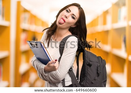 Student woman taking out her tongue in a library