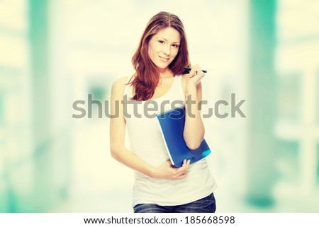 Student woman with note pad and pen isolated on white background  - stock photo