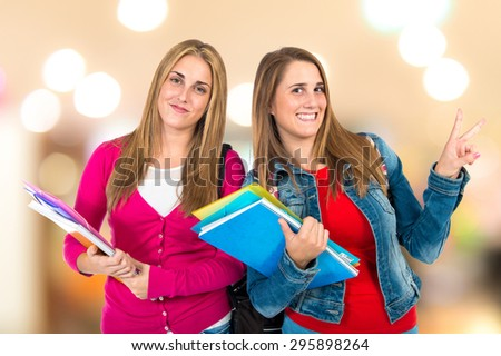 Student women doing victory gesture on unfocused background