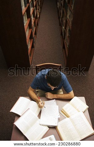 Student Working on Homework in Library - stock photo