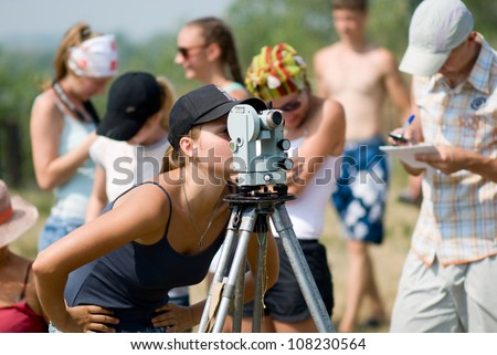 Student works with a theodolite at practice - stock photo