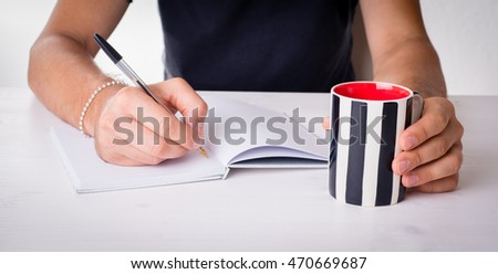 Student writing on a blank notebook with a  mug and books