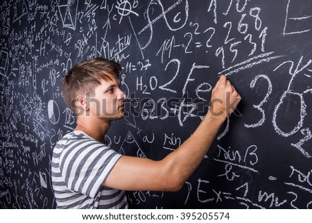 Student writing on big blackboard with mathematical symbols