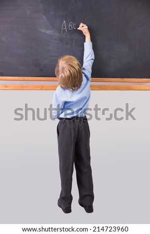 Student writing on large blackboard in school - stock photo