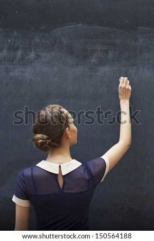 student writing on the chalkboard - stock photo