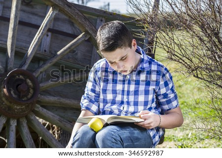 Student.Young man reading a book in outdoor with yellow apple.