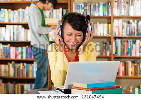Student - Young woman in library with laptop and headphones learning, a male student standing in the Background reads a book - stock photo