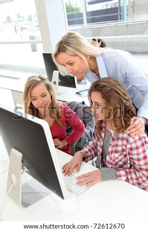 Students and teacher in in front of computer at school - stock photo