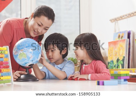 Students and teacher looking at globe