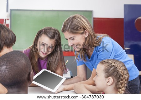 Students and teacher looking at tablet - stock photo