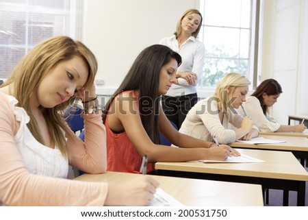 Students and tutor in exam - stock photo