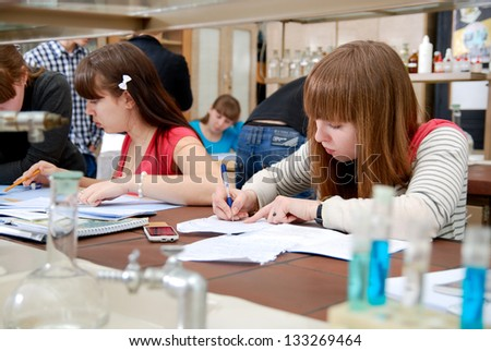 Students at work in the laboratory of chemistry take notes in a notebook - stock photo