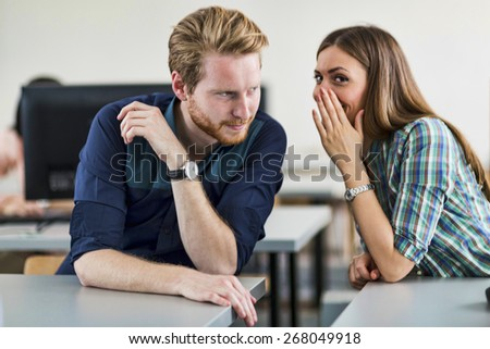 Students cheating by whispering to each other in a classroom - stock photo