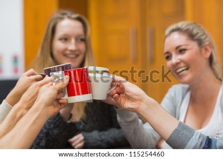 Students clinking cups while smiling in college - stock photo