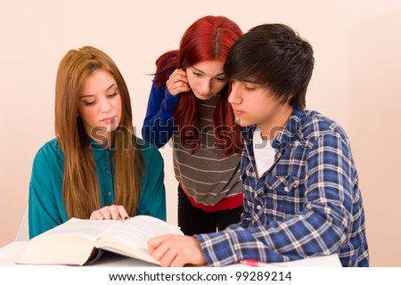Students concentratedly sitting around a book - stock photo