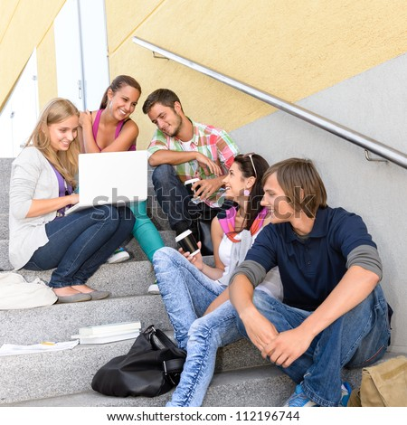 Students enjoying break on school steps laptop happy teens college - stock photo