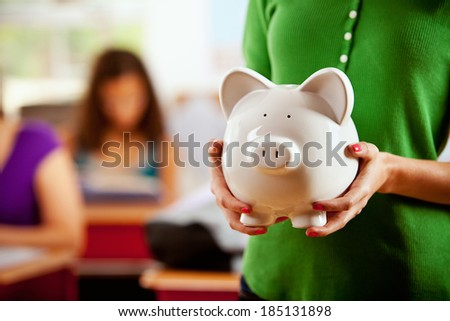 Students: Female Student Holding Piggy Bank - stock photo