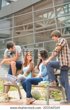 Students friends sitting bench in front of university hanging out - stock photo