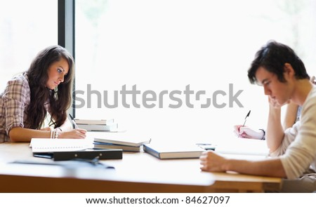 Students getting set for the examination in the library - stock photo