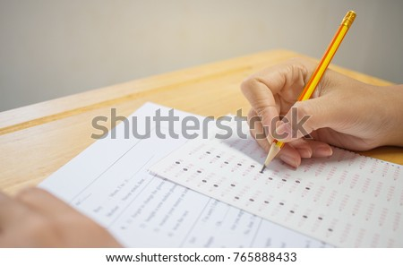 Students hands taking exams, writing examination room with holding pencil on optical form of standardized test with answers and english paper sheet on row desk chair doing final exam in classroom.