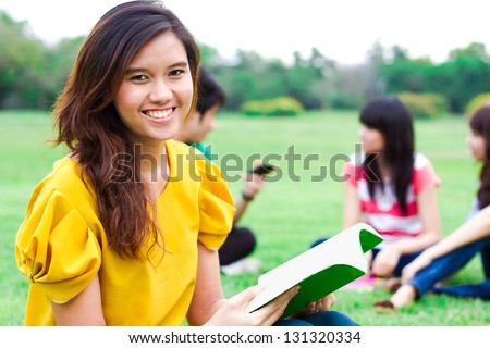 Students hanging out in the park. - stock photo