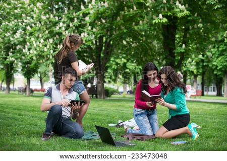 students having lesson outdoor, Students read a book in the park - stock photo