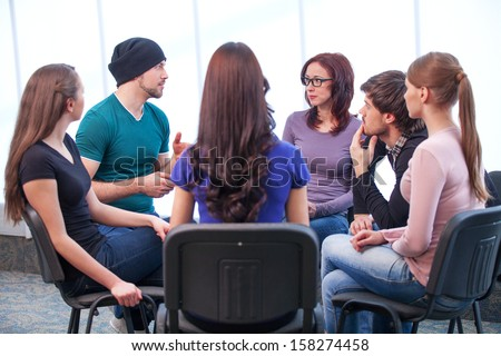Students having workshop. Young man talking while all listening  - stock photo