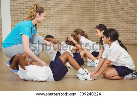 Students helping other students exercise at the elementary school - stock photo