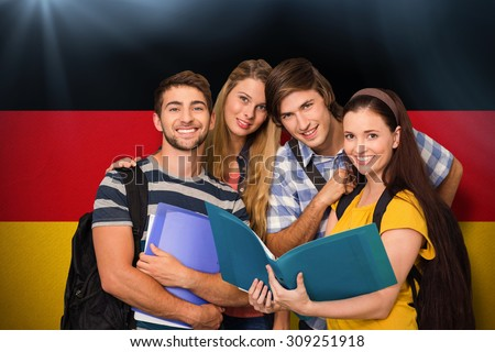 Students holding folders at college corridor against germany national flag - stock photo