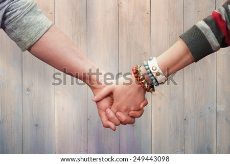 Students holding hands against pale grey wooden planks