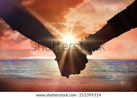 Students holding hands against sunrise over magical sea - stock photo