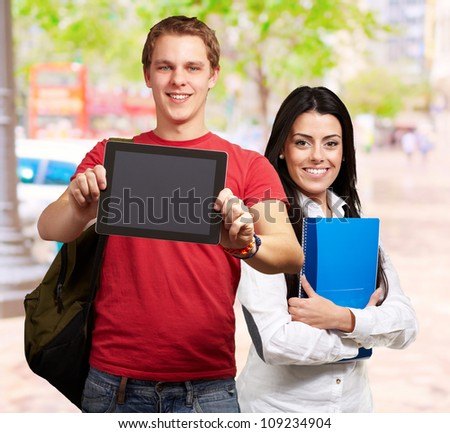 students holding tablet and books, outdoor