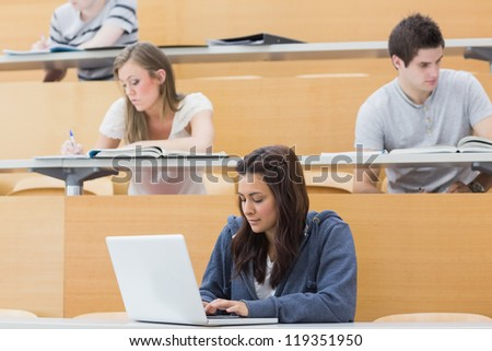 Students in a lecture hall taking notes with one using laptop - stock photo
