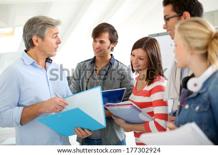 Students in school hallway asking questions to teacher - stock photo