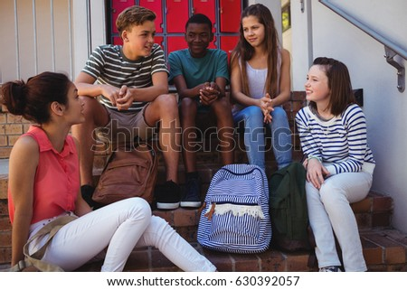 Students interacting with each other on staircase at school