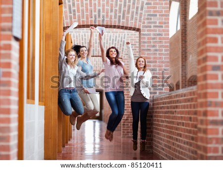 Students jumping with their results in a corridor - stock photo