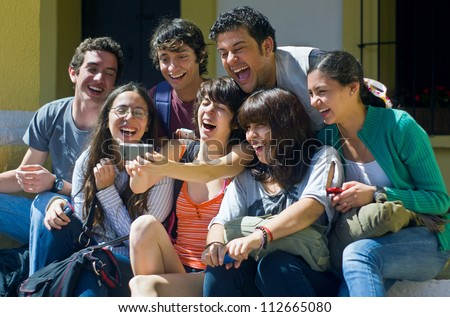 Students laughing while looking at cell phone - stock photo