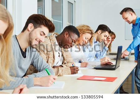 Students learning with teacher together in a school workshop - stock photo