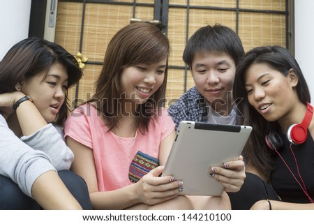 Students looking at tablet computer - stock photo